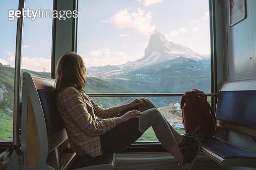 Young Caucasian woman traveling on the train near Matterhorn, Swiss Alps - gettyimageskorea