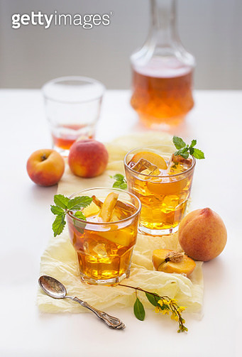 Chilled peach tea in glass with fresh cut peaches on white background. Shallow depth of field. - gettyimageskorea