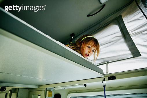 Young girl leaning over edge of bed in camper van - gettyimageskorea
