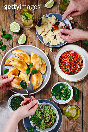 Traditional mexican food - Meat Empanadas with Cilantro Chimichurri Sauce,  Guacamole, Salsa, Tortilla Chips and Mojito. Couple eating mexican food - gettyimageskorea