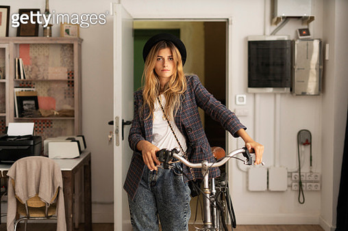 Portrait of a young woman with bicycle in a studio - gettyimageskorea
