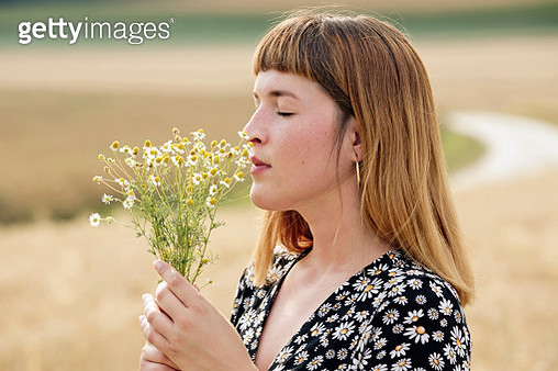 Young woman with eyes closed smelling bunch of chamomile flower - gettyimageskorea