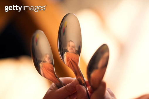 Child pulling silly face, reflected in spoons - gettyimageskorea