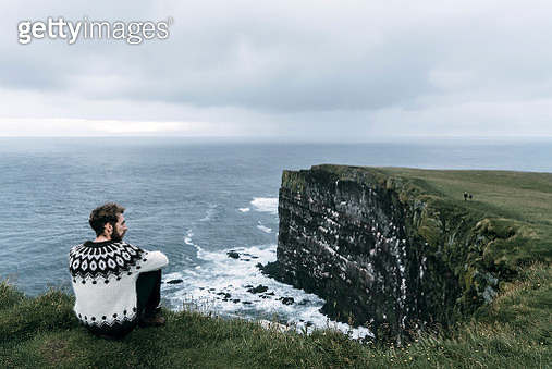 Man looking at scenic view from the cliff in Iceland - gettyimageskorea