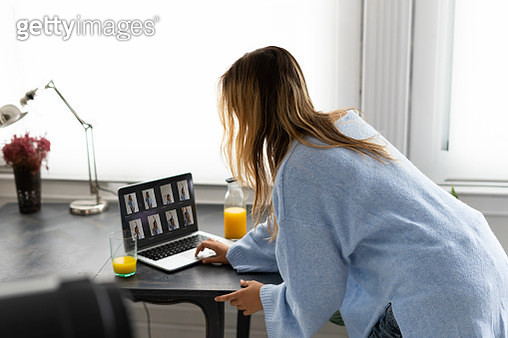 Young woman looking at photos on laptop - gettyimageskorea