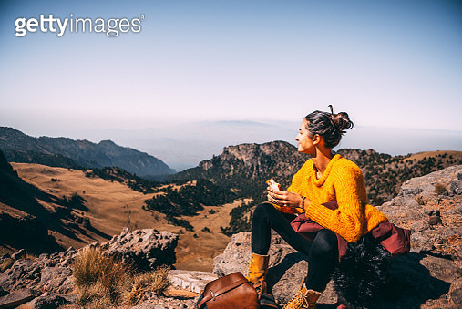 Tired Latin woman making a launch break. She is hiking at Popocatepetl volcano in Mexico - gettyimageskorea