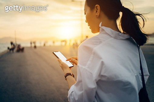 Young lady using smartphone while having a relaxing walk by the pier afterwork at sunset - gettyimageskorea