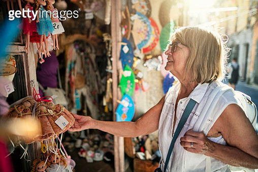 Senior woman tourist browsing and buying souvernirs at street market stand at Salerno. Region of Campania in Italy. - gettyimageskorea