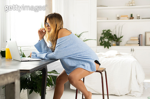 Young woman sitting in bedroom at home using laptop - gettyimageskorea