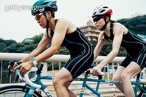 Visually impaired female triathlete training together with her guide and coach on a tandem bicycle - gettyimageskorea