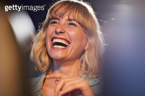 Young woman laughing while enjoying comedy movie in theater - gettyimageskorea