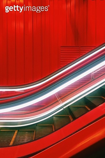 Close-Up Of Illuminated Escalator By Red Wall - gettyimageskorea