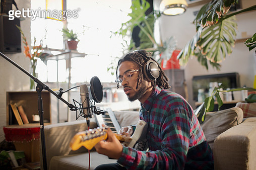 Young male musician recording music, playing guitar at microphone in apartment - gettyimageskorea