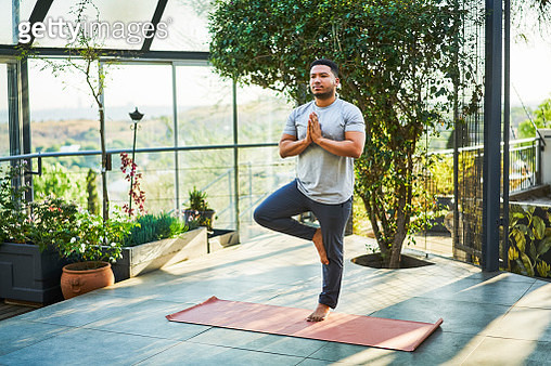 Young man practicing tree pose on exercise mat - gettyimageskorea