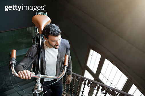 Young entrepreneur businessman arriving in the office carrying his bike - gettyimageskorea