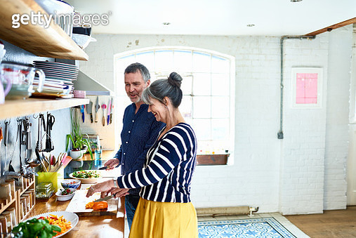 Mature couple preparing vegetarian meal in stylish kitchen - gettyimageskorea