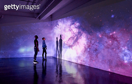 Couple Looking at Large Scale Projected Image of Space - gettyimageskorea
