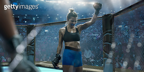 A close up composite image of a professional female mixed martial arts fighter dressed in tight shorts, sports bra, and grappling gloves. The fighter is wearing a mouth guard and raising her fist whilst screaming in victory. She stands in an octagon cage  - gettyimageskorea
