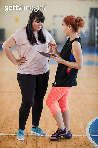 Fitness instructor with digital tablet talking with woman in gym - gettyimageskorea