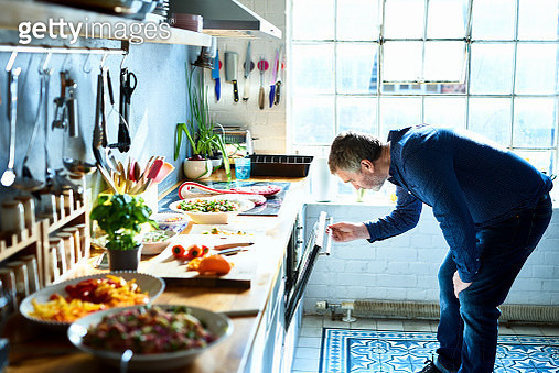 Man in his 50s making dinner in stylish loft apartment kitchen, healthy lifestyle, vegetarian, care, leisure - gettyimageskorea