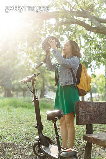 Young woman standing outside and holding helmet - gettyimageskorea