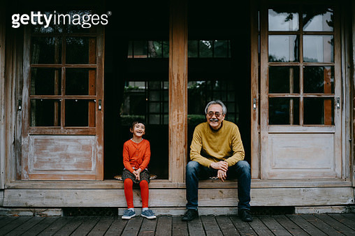Portrait of Japanese grandfather and cute preschool granddaughter sitting on patio and laughing at camera - gettyimageskorea