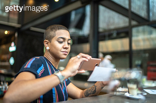 Young woman depositing check by phone in the cafe - gettyimageskorea