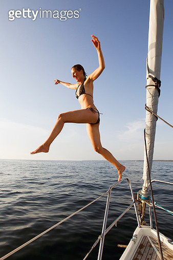 Woman jumping off boat into water - gettyimageskorea