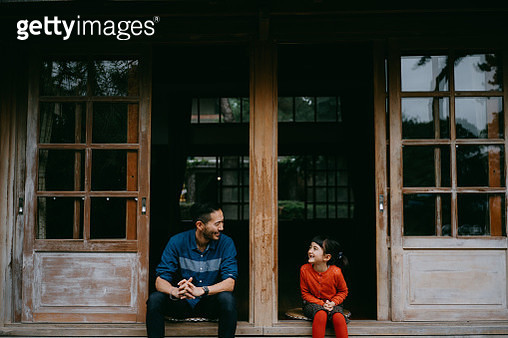 Japanese father and his cute preschool daughter sitting on patio and smiling at each other - gettyimageskorea