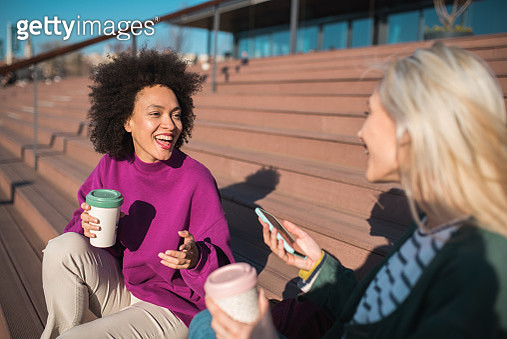 Young women having coffee to go on and using smart phone on vacation - gettyimageskorea