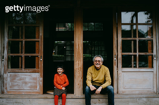 Japanese grandfather and his cute Eurasian granddaughter sitting on patio - gettyimageskorea