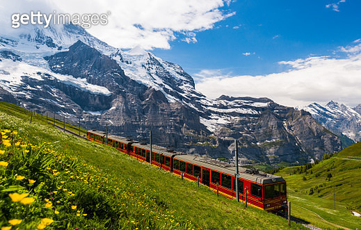 The red train running on the Jungfrau railway between the Bernese Oberland and Valais in Switzerland. - gettyimageskorea