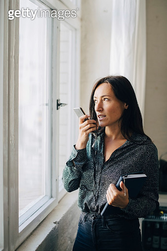 Creative businesswoman talking on mobile phone while standing by window in office - gettyimageskorea