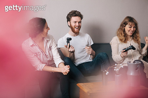 Excited young friends playing video games at home - gettyimageskorea