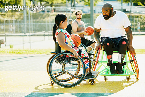 Smiling young female adaptive athlete getting advice from adaptive basketball coach during practice on summer evening - gettyimageskorea