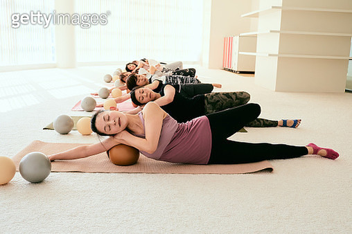 Female instructor leading pilates classroom in fitness studio - gettyimageskorea