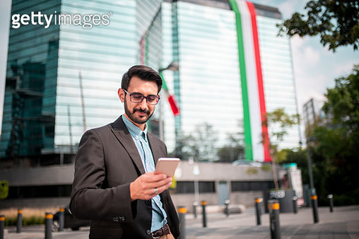 Young businessman standing at a city street and using a mobile phone - gettyimageskorea
