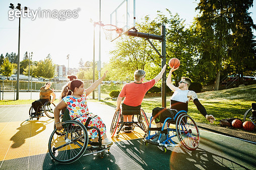 Adaptive athlete playing pickup wheelchair basketball on outdoor court on summer evening - gettyimageskorea