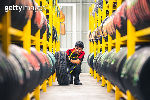 mechanic pulls tire from the tyre store warehouse - gettyimageskorea