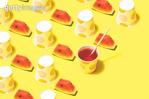 Disposable paper cups on color background. Watermelon juice and polka dot paper cups flat lay on yellow background - gettyimageskorea