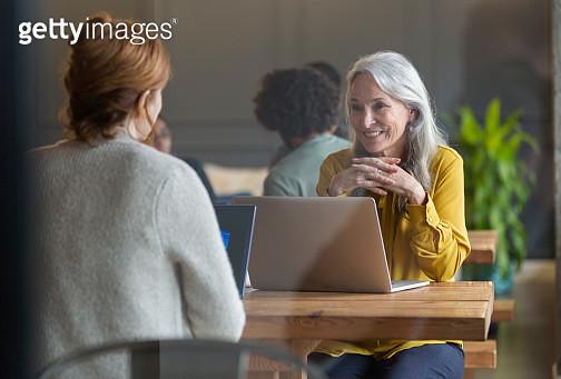 Business woman using laptop in modern open plan office - gettyimageskorea