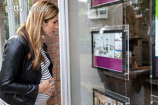 Pregnant mid adult woman looking through estate agents window - gettyimageskorea
