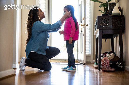 Mother putting mask on daughter - gettyimageskorea
