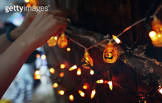 Woman hanging decorative eletric light with pumpkins. Halloween theme - gettyimageskorea
