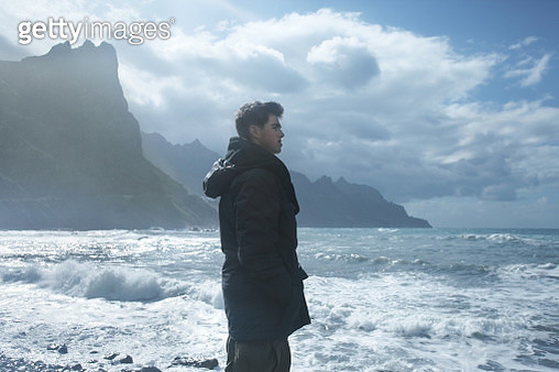 Man looking at stormy sea, cliffs in background - gettyimageskorea