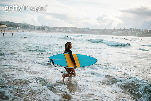 Portrait of skilled female surfer running into waves in Hawaii - gettyimageskorea