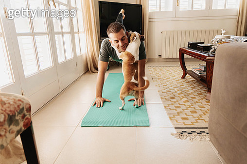 Doing exercise at home with dog during Coronavirus quarantine. COVID-19. - gettyimageskorea