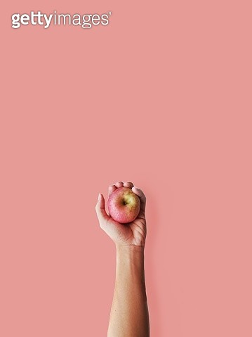 Cropped Hand Holding Apple Against Coral Background - gettyimageskorea