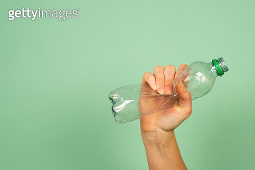 Hand Holding Smashed Memory Plastic Bottle Against Green Background.  Concept For Recycling. - gettyimageskorea