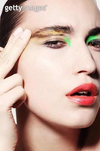 Woman smudging bright coloured make up on face - gettyimageskorea